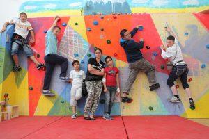 Acht Kinder klettern an einer selbstgestalteten bunten Kletterwand.