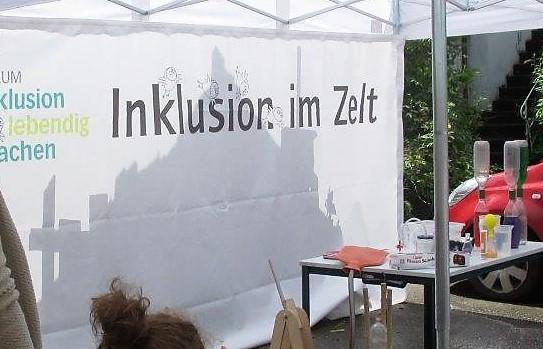 Eine weiße Pavillionrückwand mit der Aufschrift Inklusion im Zelt, davor ein Tisch mit Experimentiermaterial