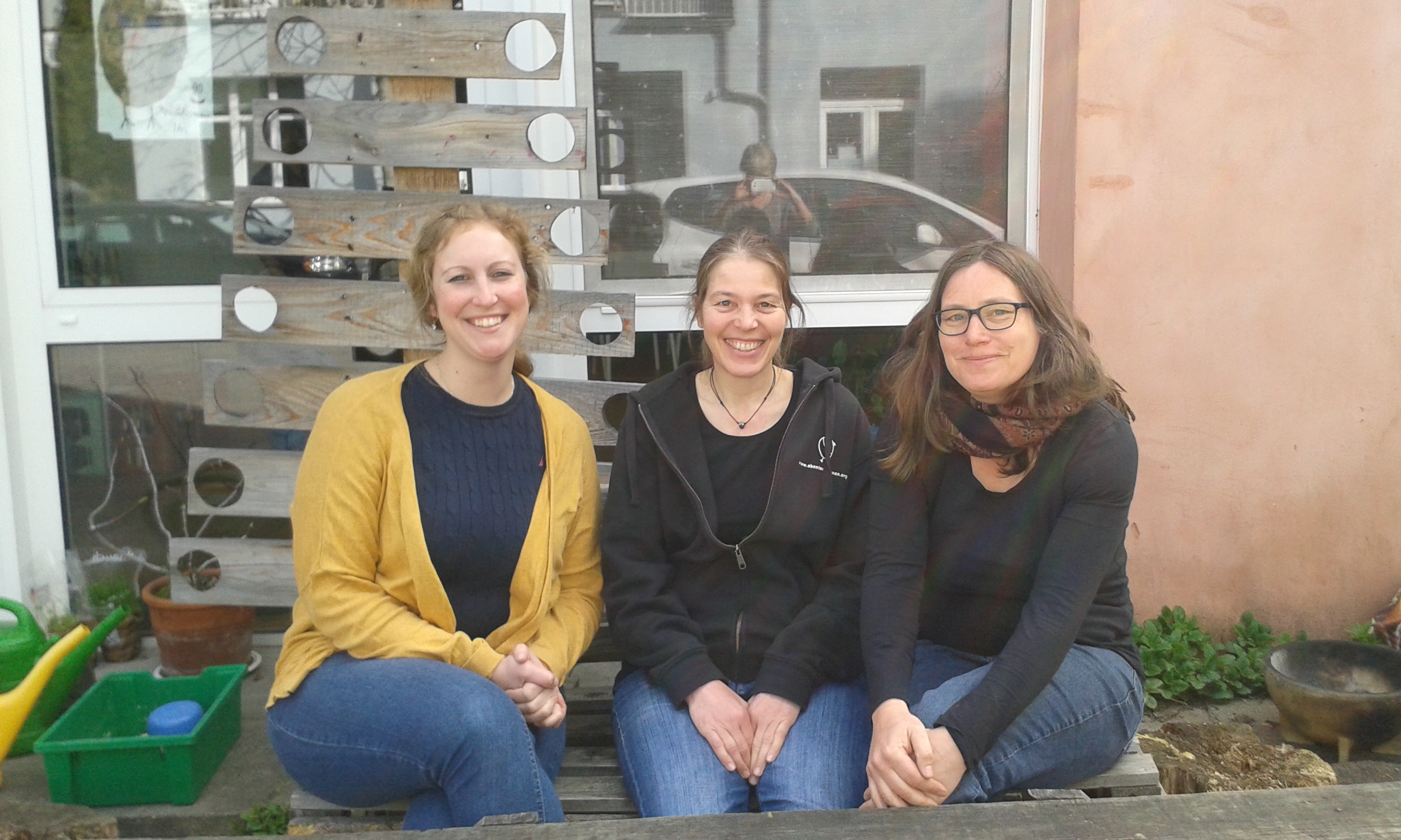 Die Leiterin der Jugendfarm, die pädagogische Leiterin von Abenteuer Lernen und die Projektleiterin des Forums Inklusion lebendig machen sitzten vor den Räumen von Abenteuer Lernen.