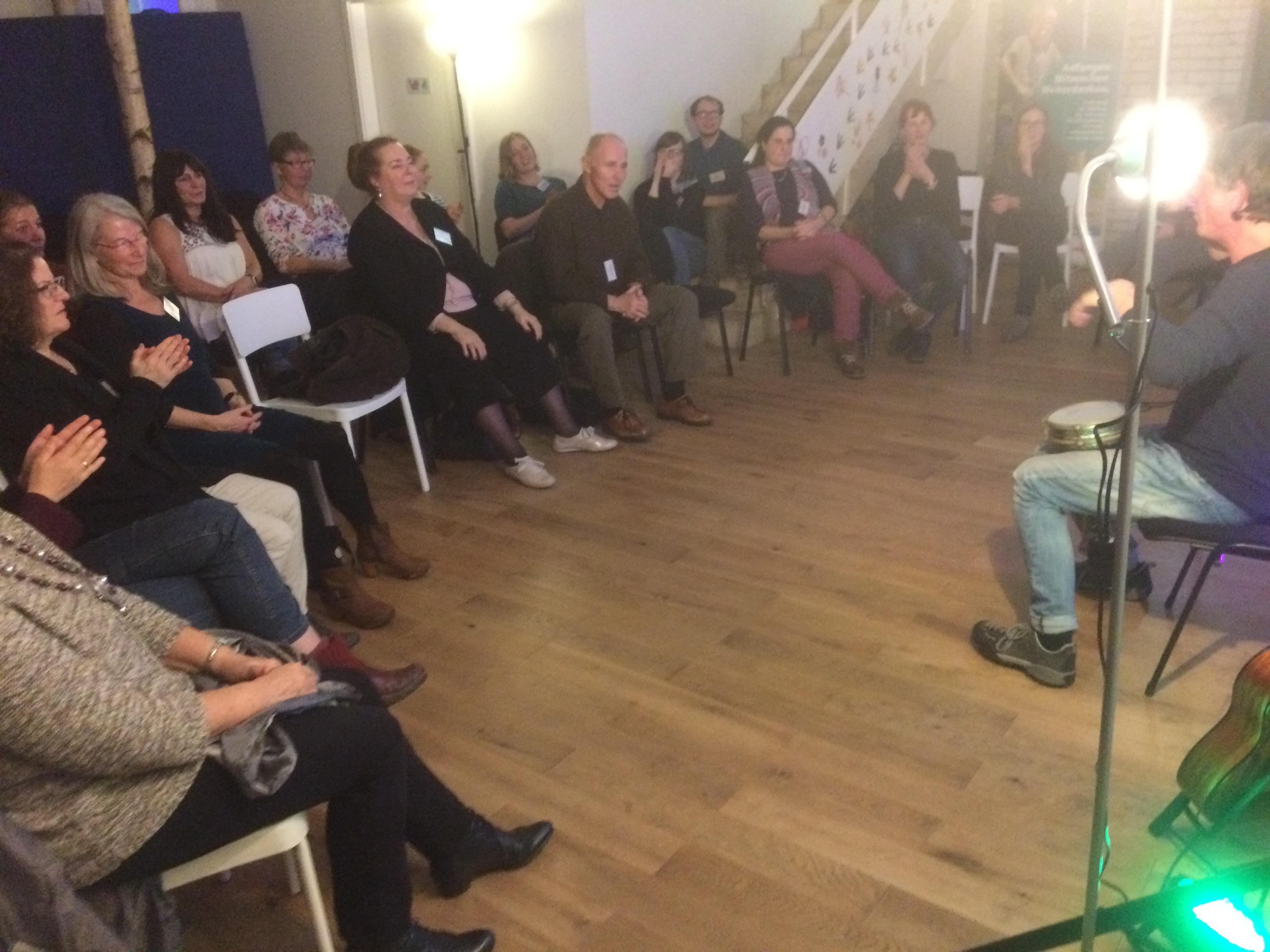 Das Publikum sitzt im Halbkreis und lauscht gespannt dem Mitmachprogramm.