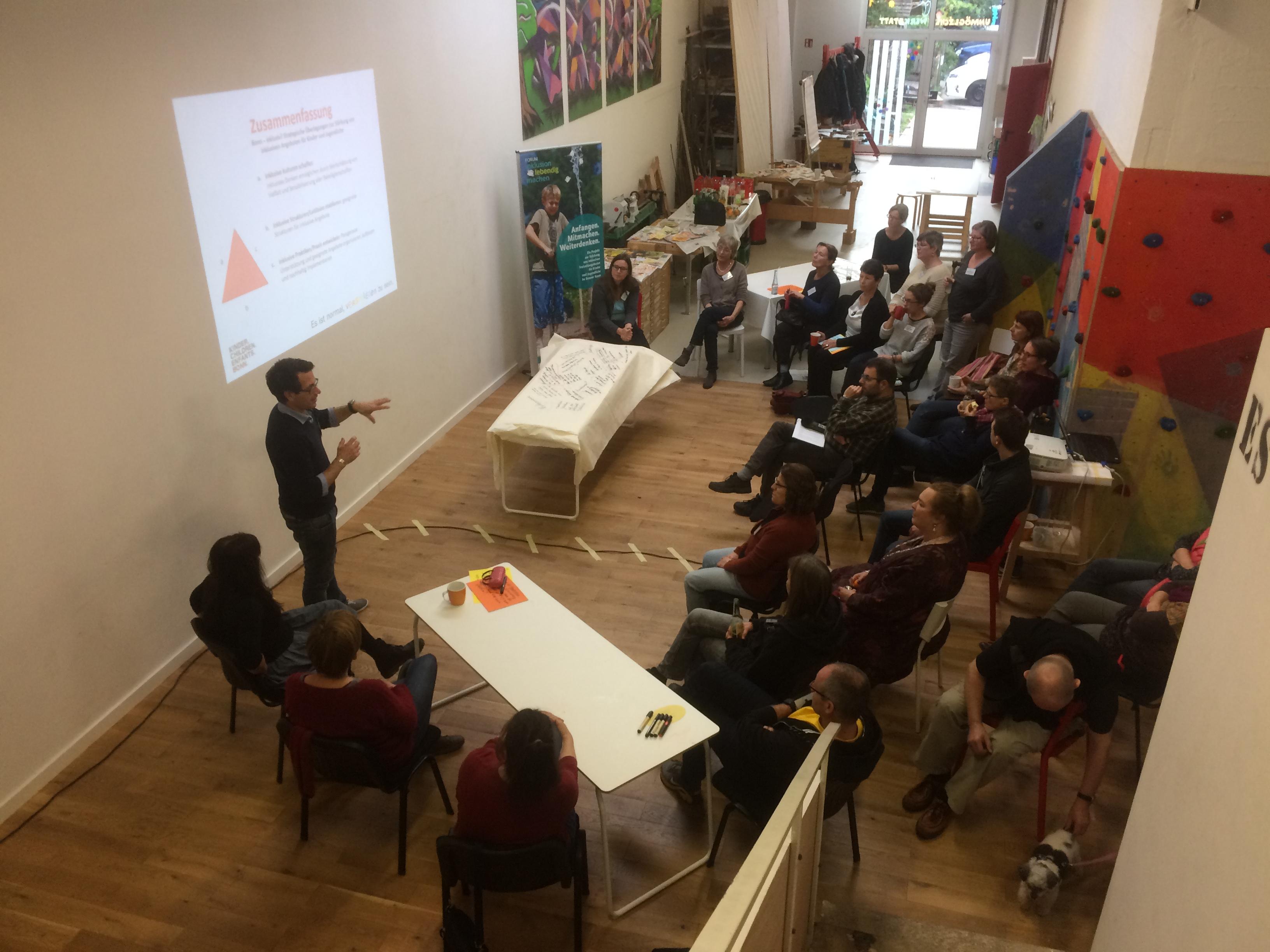 Ein Blick von oben auf die Werkstatträume von Abenteuer Lernen. Ungefähr vierzig Personen sitzen und hören einem Redner zu, der die Vorgehensweise des Worldcafes erläutert. Mit einem Beamer ist an einer Wand ein Schaubild projeziert.