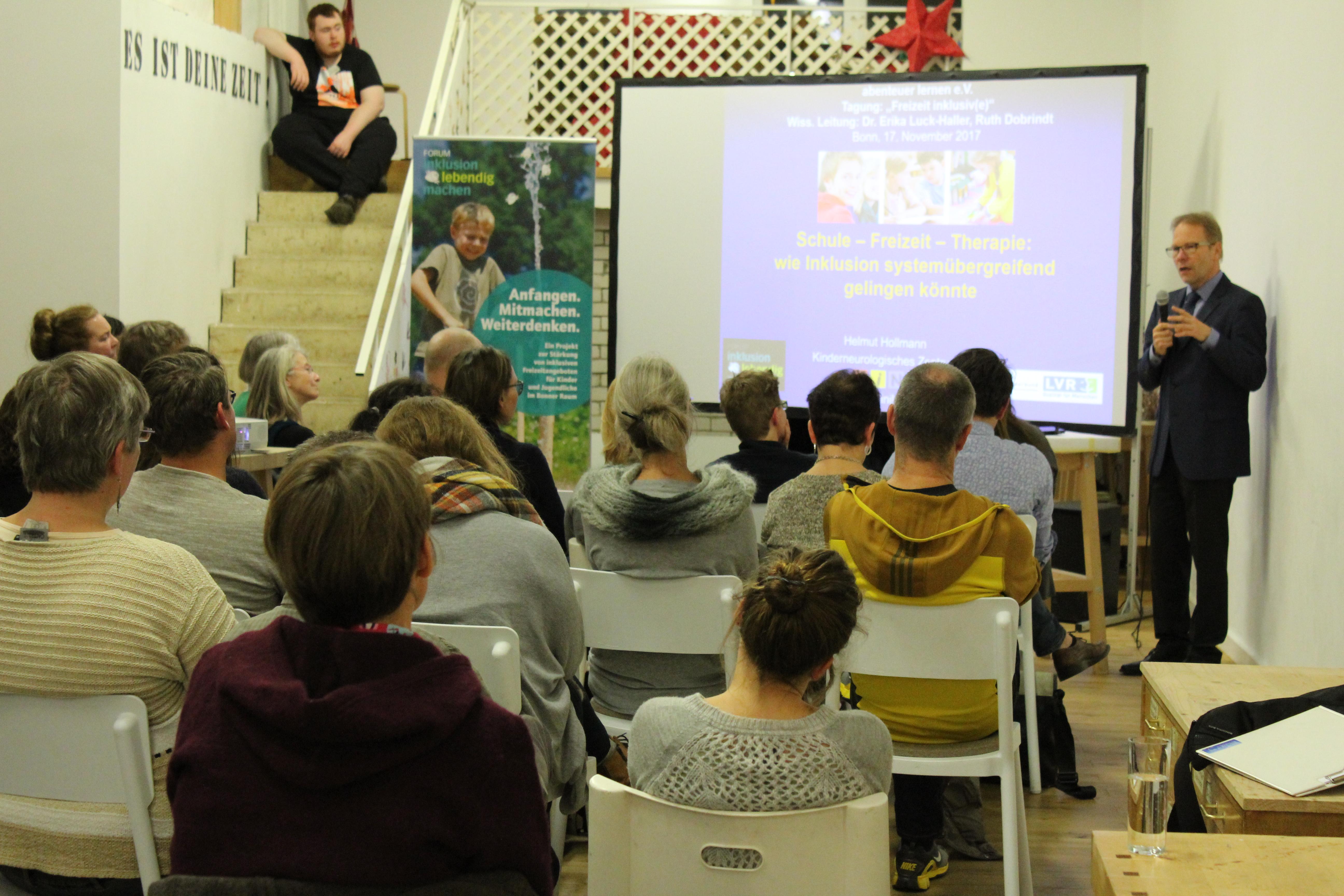 Im Hintergrund sieht man eine Leinwand auf der ein Vortrag projeziert wird. Im Vordergund sitzten viele Teilnhemer auf Stühlen.