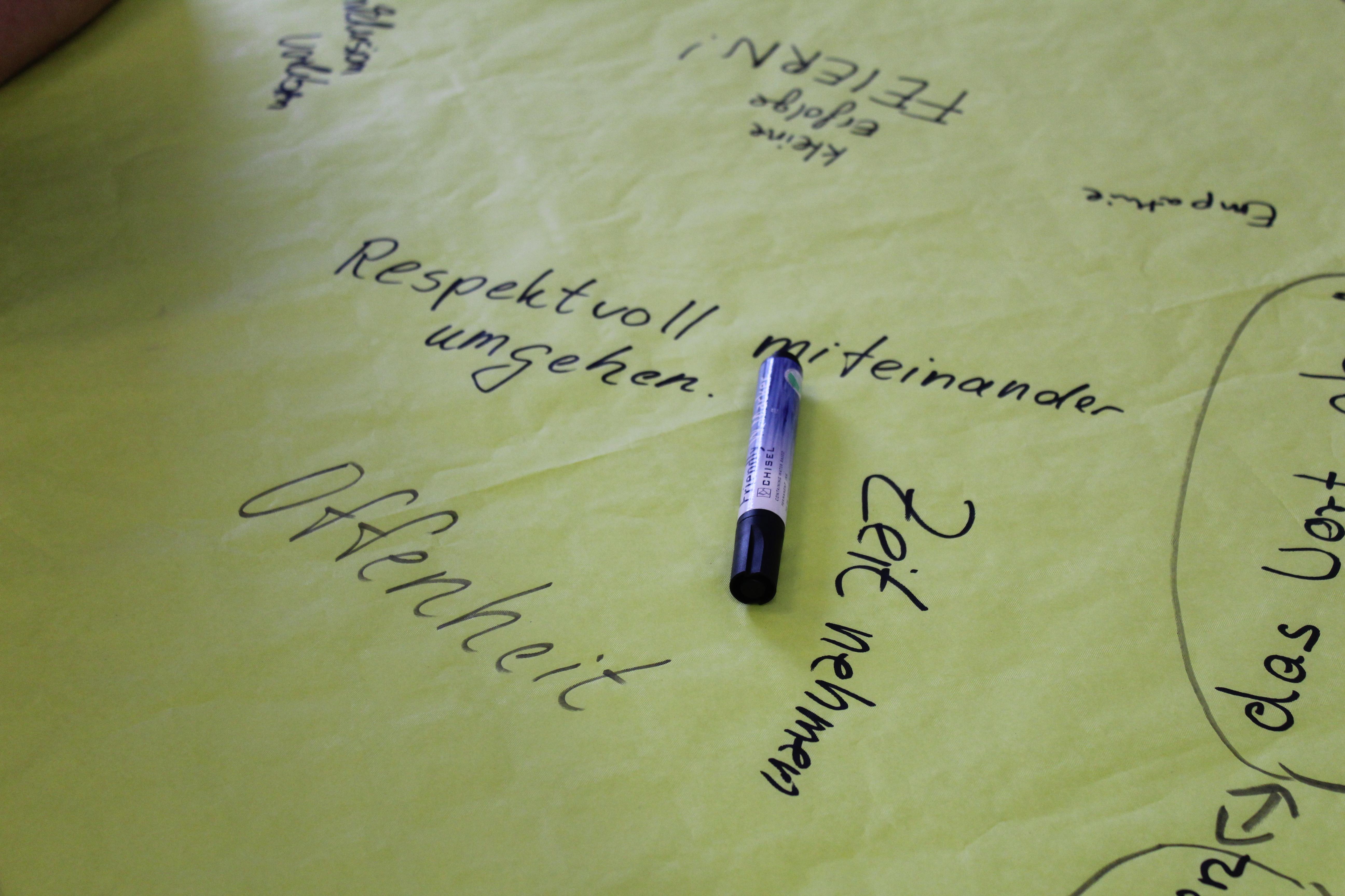 """Auf einer gelben Papiertischdecke sind verschiedene Begriffe mit Edding geschrieben: """"Offenheit"""", """"Zeit nehmen"""" und """"respektvoll miteinander umgehen""""."""